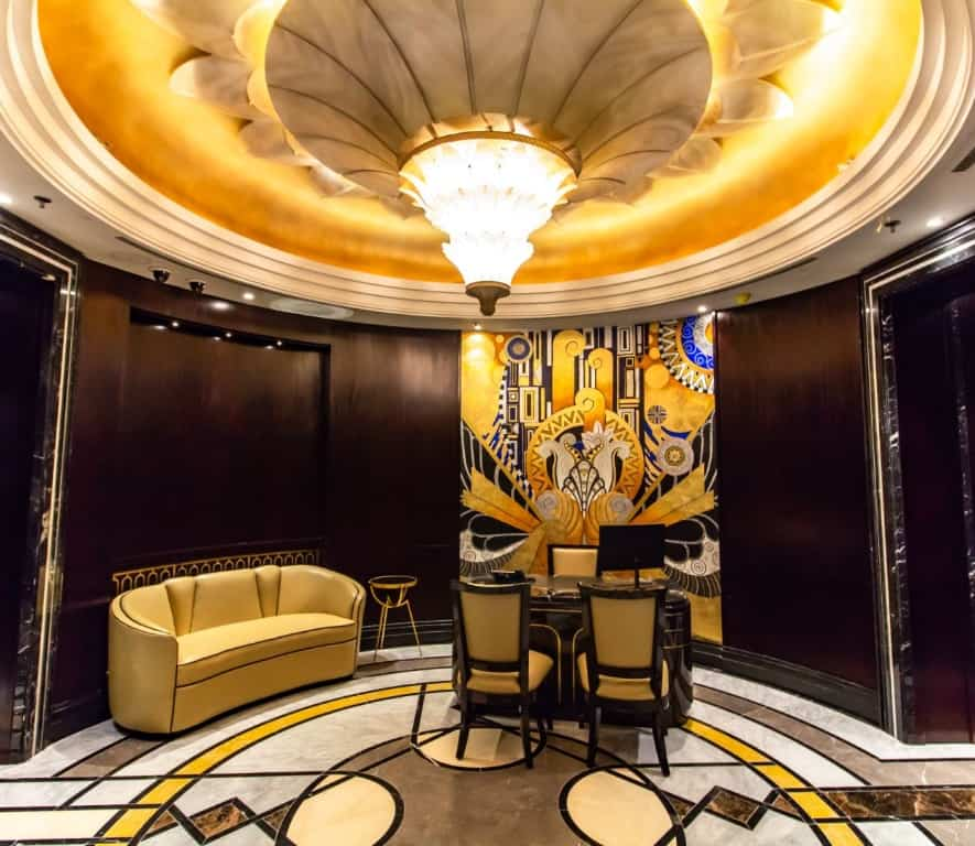 Salon Privé with golden decor and large artwork in the hallway