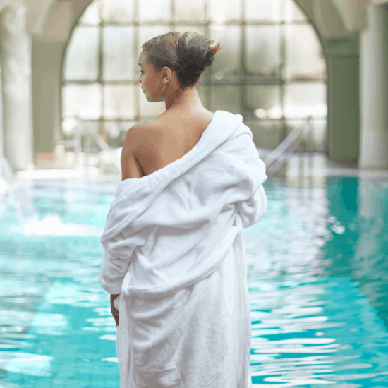 Women wearing a white robe by the spa pool